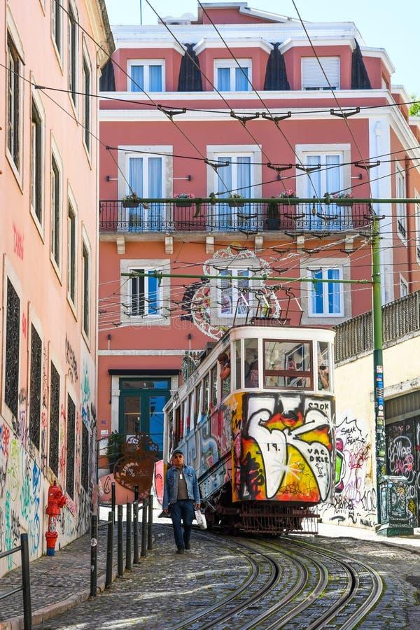 Elevador da Gloria in Lisbon. Colorful Elevador da Gloria going through narrow streets in Lisbon. Europe. Elevador da Gloria is a very old public transport stock photo