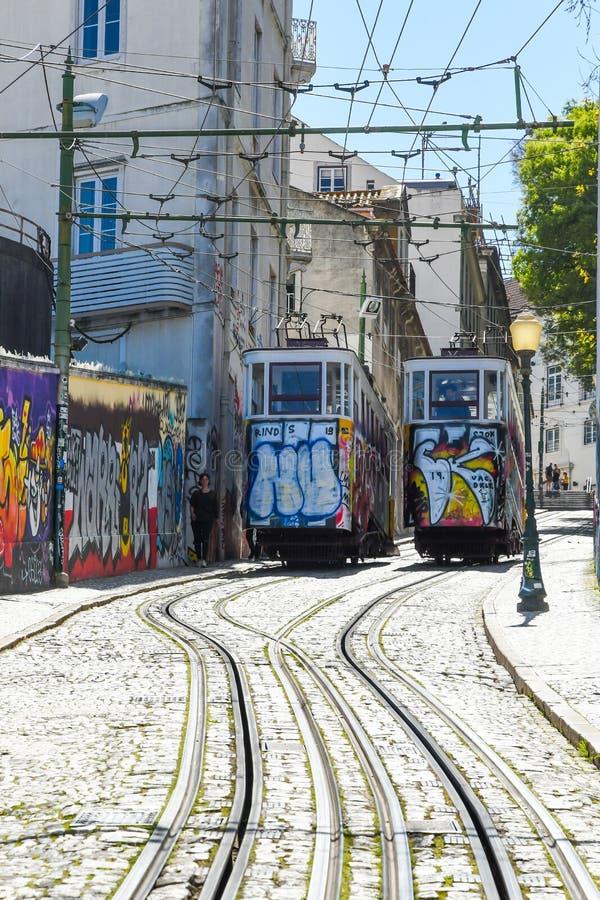 Elevador da Gloria in Lisbon. Colorful Elevador da Gloria going through narrow streets in Lisbon. Europe. Elevador da Gloria is a very old public transport stock photography