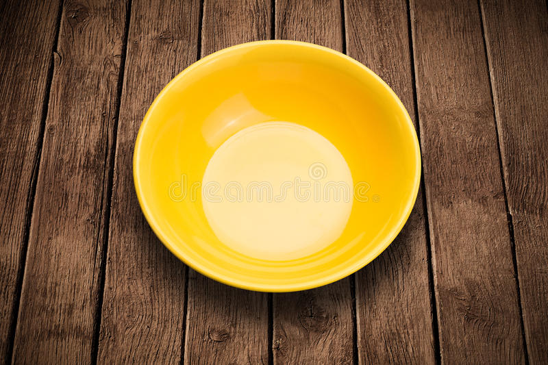 Colorful empty plate on grungy background table. Colorful empty shiny plate on grungy background table royalty free stock image