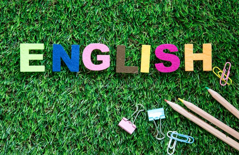Colorful ENGLISH word cube on green grass yard background ,English language learning concept stock photography