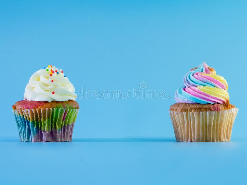 Colorful and enteresting cupcake isolated on blue background studio close up shot. Colorful and enteresting cupcake isolated on blue background studio close up royalty free stock images
