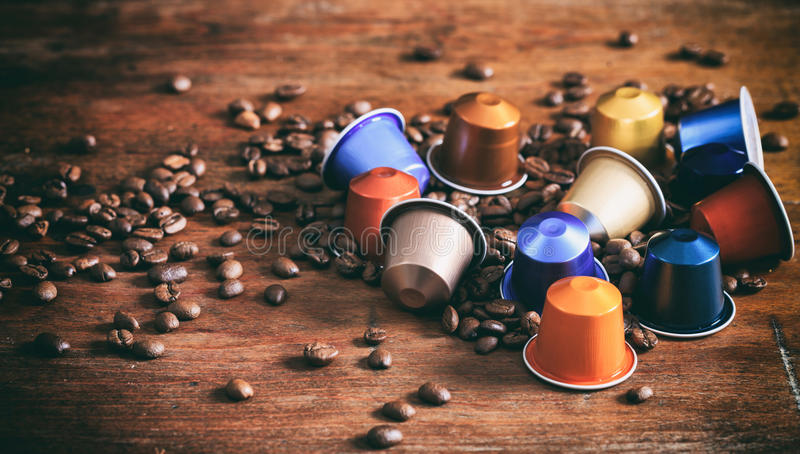 Colorful espresso capsules on wooden background royalty free stock images