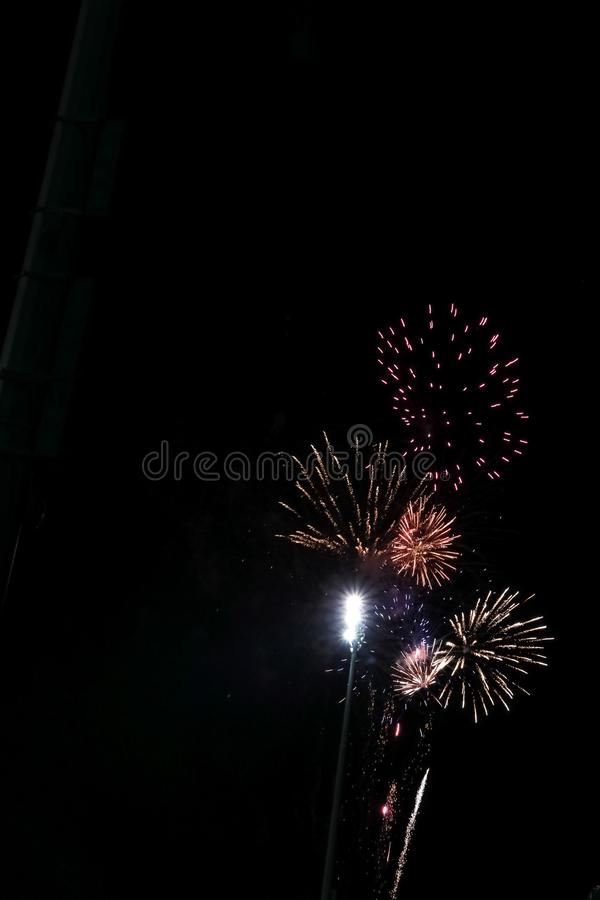 Colorful explosion of fireworks along bright lights of football game stock photos