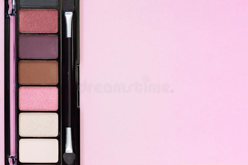 Colorful Eye Shadow Palette Makeup Products on pastel pink background with copy space. royalty free stock photo