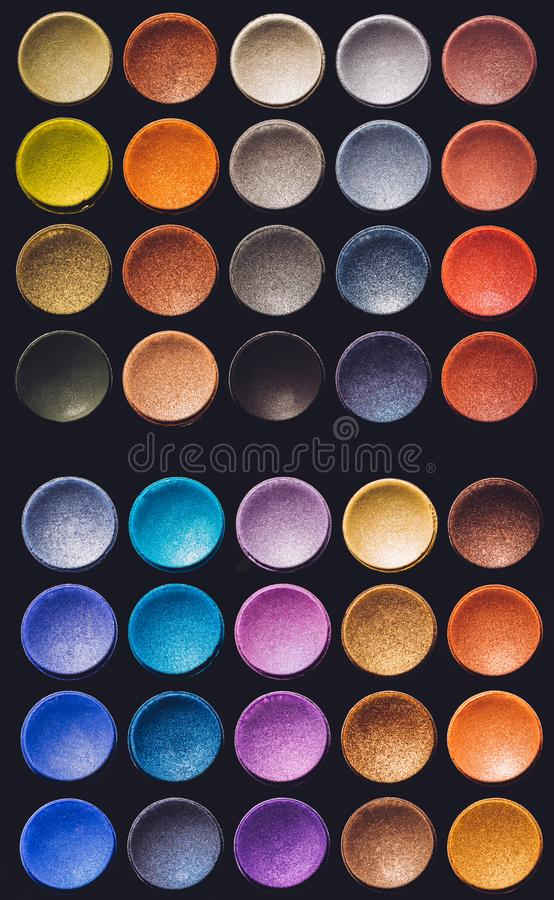Colorful eyeshadow set on a black background. Flat lay. Multicolored beauty products stock photography