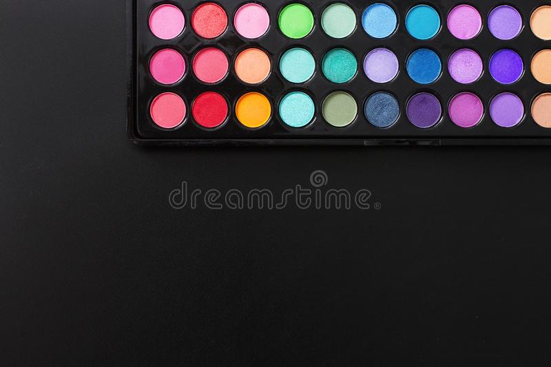 Colorful eyeshadows on black background. Summer fashion trend. Top view and copy space.  royalty free stock photo