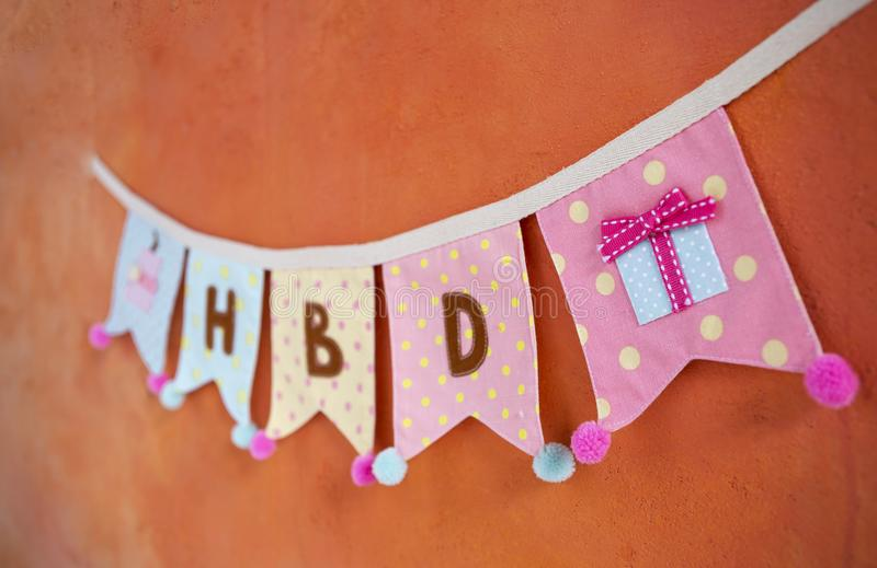 Colorful fabric birthday party flag hanging on orange cement wall stock photos