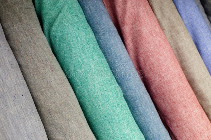 Colorful fabric swatches on shopfront. A lot of fabric rolls. Textile samples background. Bolts of linen cloth pastel shades royalty free stock photos