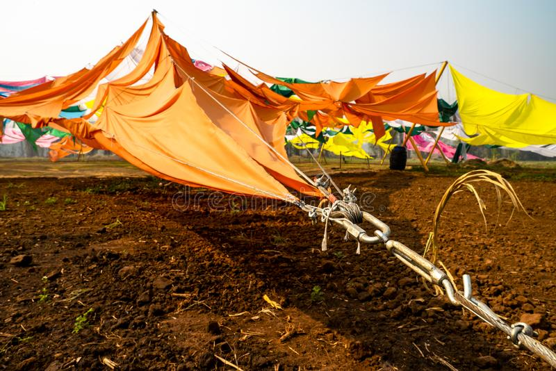 Colorful fabric tents being tied with chains to the ground. stock photo