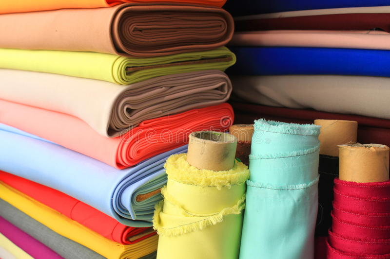 Colorful fabrics. Textile arranged vertically and rolls in front royalty free stock photos