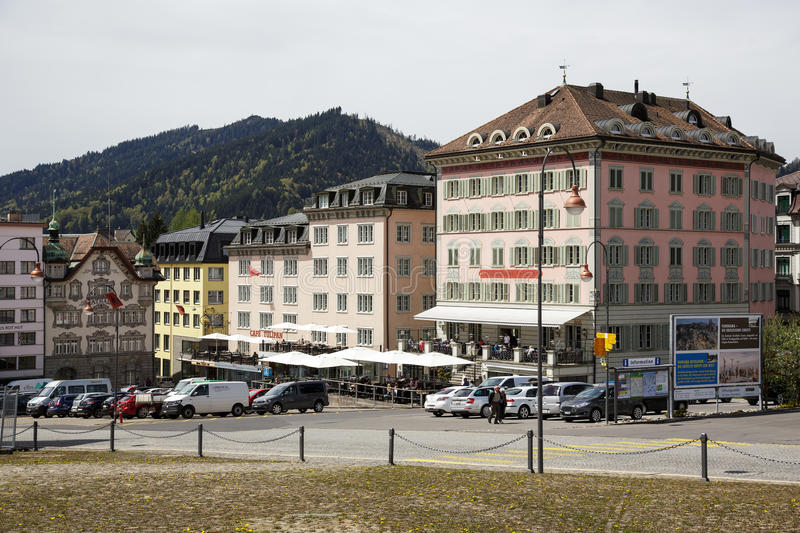 Colorful facades of buildings in Einsiedeln. EINSIEDELN, SWITZERLAND - MAY 09, 2016: Colorful facades of buildings and cars on a street shows the town that is royalty free stock image