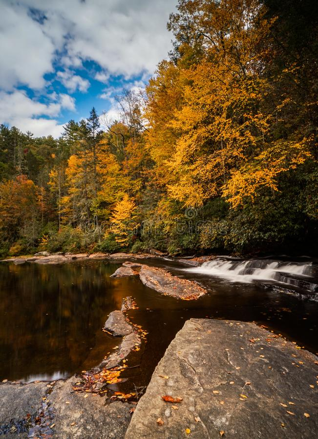 Colorful fall foliage forest and river landscape with a small waterfall stock image