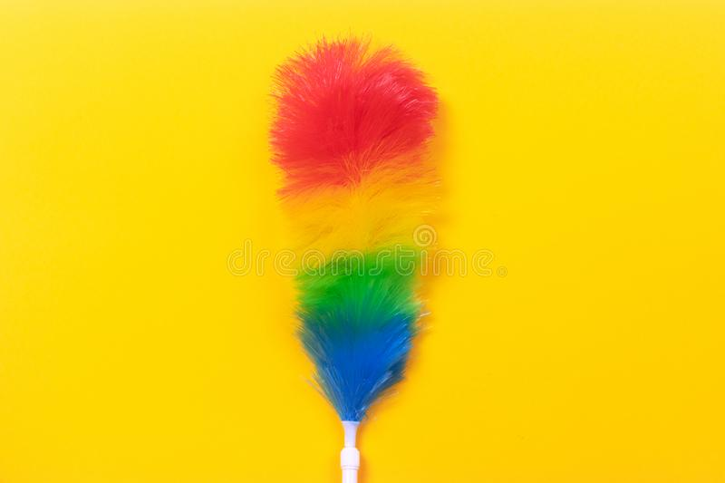 Feather duster. Colorful feather duster on yellow background. Cleaning concept royalty free stock image