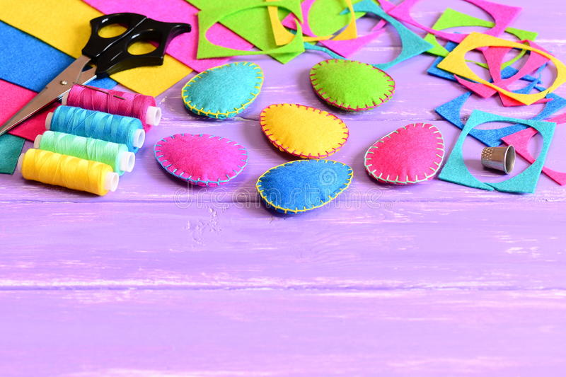 Colorful felt Easter eggs decorations, felt sheets and scraps, scissors, thread, thimble on a table. Easy Easter sewing crafts stock photos