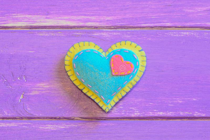 Colorful felt heart on a purple wooden background with copy space. Valentine backdrop. Happy Valentines Day heart. Valentines Day heart symbol. Valentine crafts stock photos