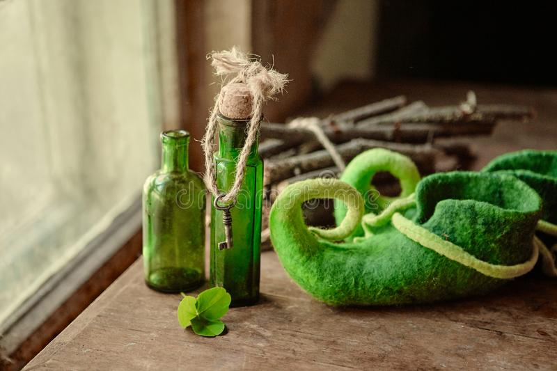 Colorful felted green shoes stand next to antique glass bottles, a leaf of clover and a bundle of firewood stock photography