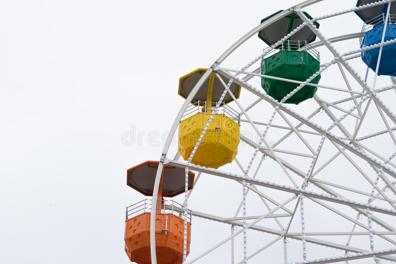 Colorful ferris wheel. Right heavy crop of a part of a colorful ferris wheel in front of a white sky stock images