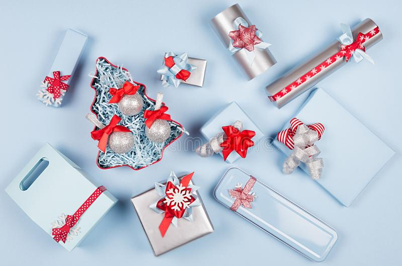 Colorful festive different gift boxes and christmas tree in red, blue and metallic color with silk ribbons and bows on light blue. Colorful festive different stock photos