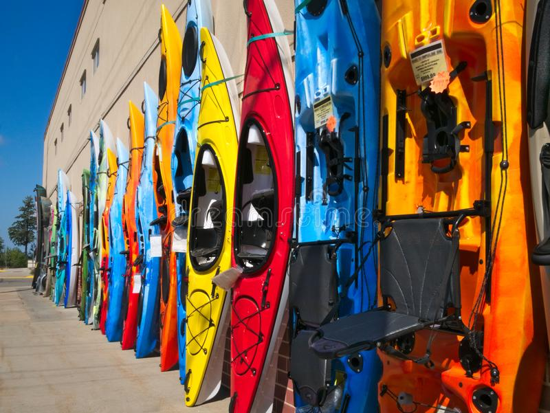 Colorful fiberglass kayaks on display outside sporting goods store. In lake country of northern Minnesota stock image