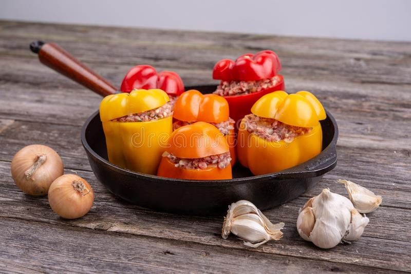 Colorful filled pepper,garlic and onion in iron pan from above. Colorful filled pepper,garlic and onion in iron pan on wooden ground from above royalty free stock photo