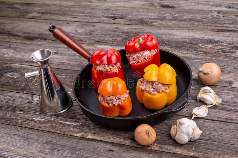 Colorful filled pepper,garlic and onion in iron pan from above. Colorful filled pepper,garlic and onion in iron pan on wooden ground from above stock photo