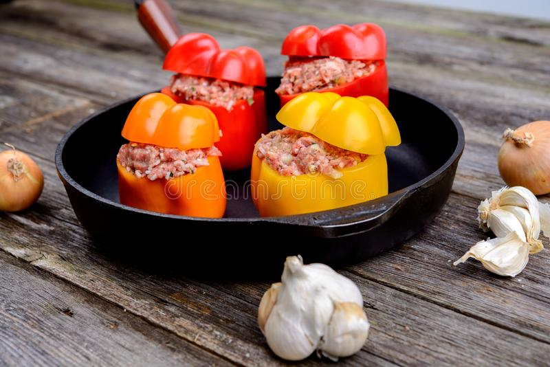 Colorful filled pepper,garlic and onion in iron pan. On wooden ground royalty free stock images