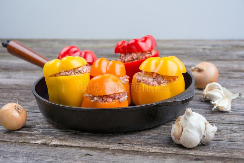 Colorful filled pepper,garlic and onion in iron pan. On wooden ground royalty free stock photography