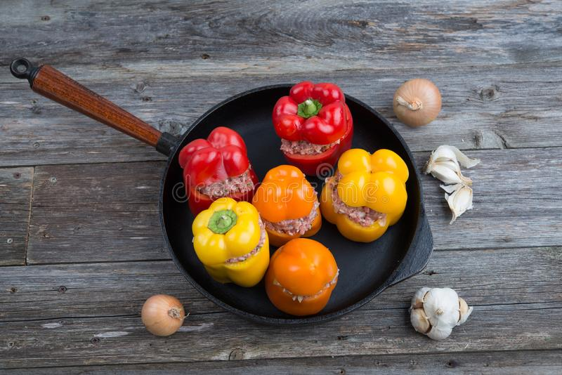 Colorful filled pepper,garlic and onion in iron pan from above. Colorful filled pepper,garlic and onion in iron pan on wooden ground from above stock images