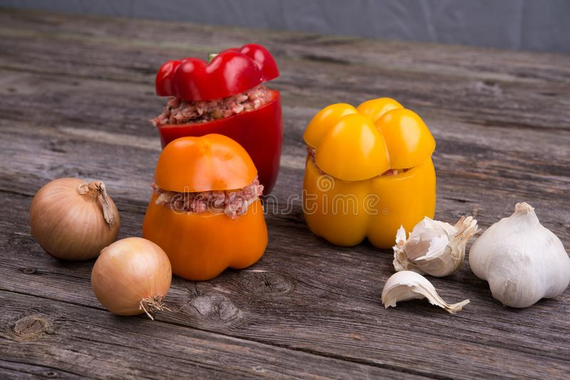 Filled pepper,garlic and onion on wooden ground. Colorful filled pepper,garlic and onion on wooden ground stock photos