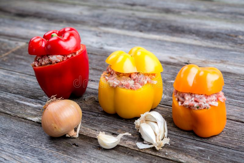 Filled pepper,garlic and onion on wooden ground. Colorful filled pepper,garlic and onion on wooden ground royalty free stock photography