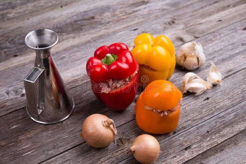 Filled pepper, oil, garlic and onion on wooden ground. Colorful filled pepper, oil, garlic and onion on wooden ground royalty free stock photo