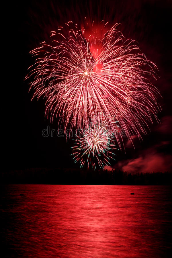 Colorful firework in a night sky. Red firework in a night sky, reflection in water stock image