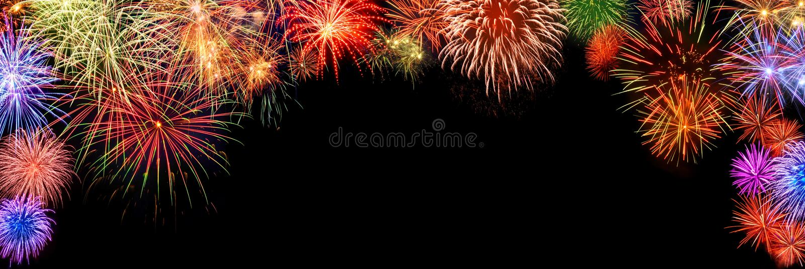 Colorful fireworks, arch shaped border on black. Spectacular multi-colored fireworks as a panoramic arch shaped border on black background, ideal for New Year or royalty free stock images