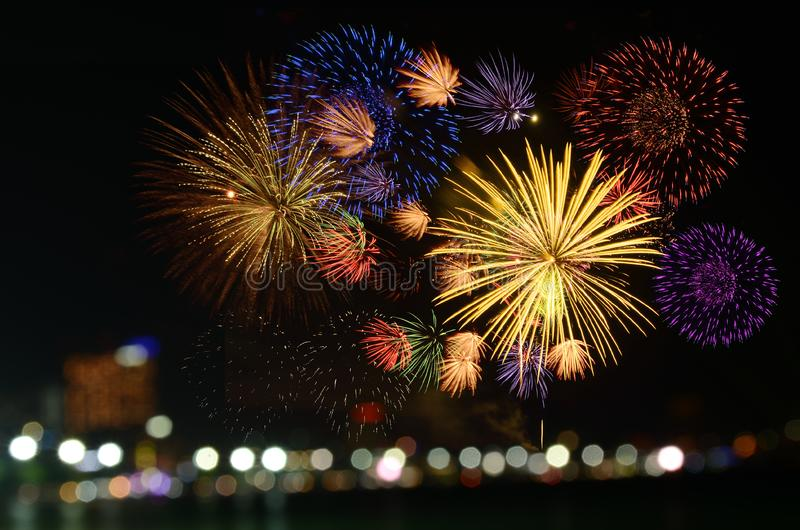 Colorful fireworks celebration and the city night light background. stock photography