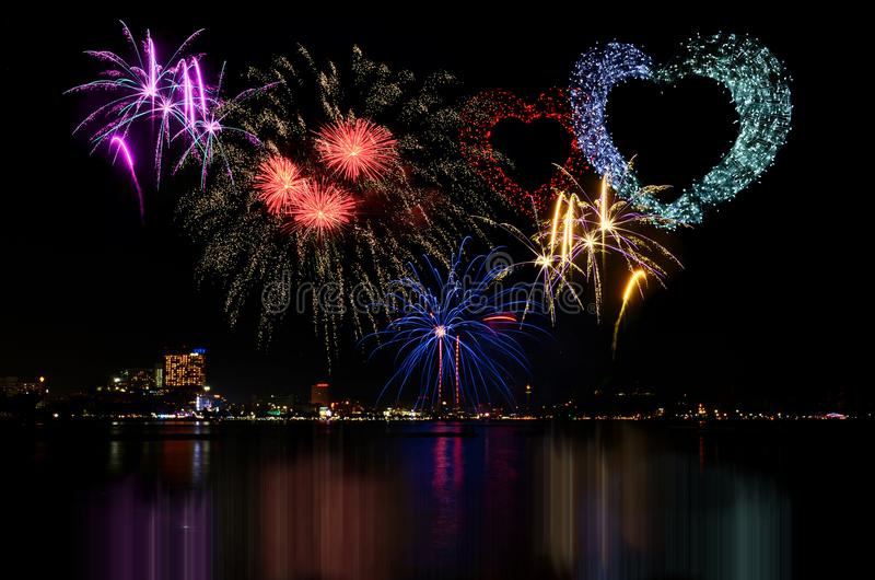 Colorful fireworks celebration and the city night light background. stock images