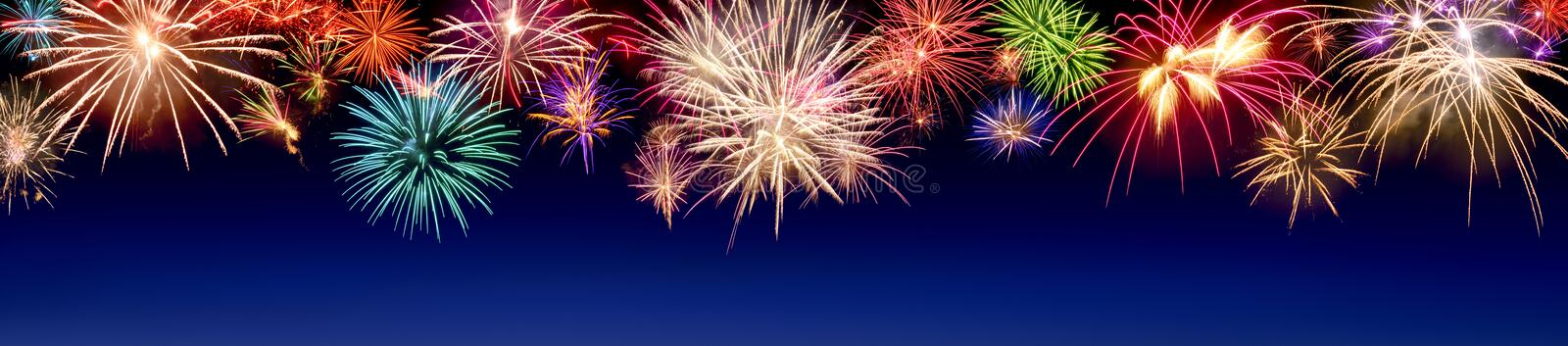 Colorful fireworks display on blue royalty free stock photography