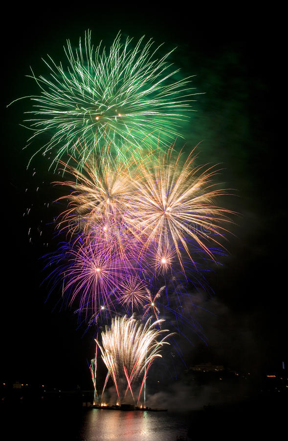 Colorful fireworks on river dam stock image