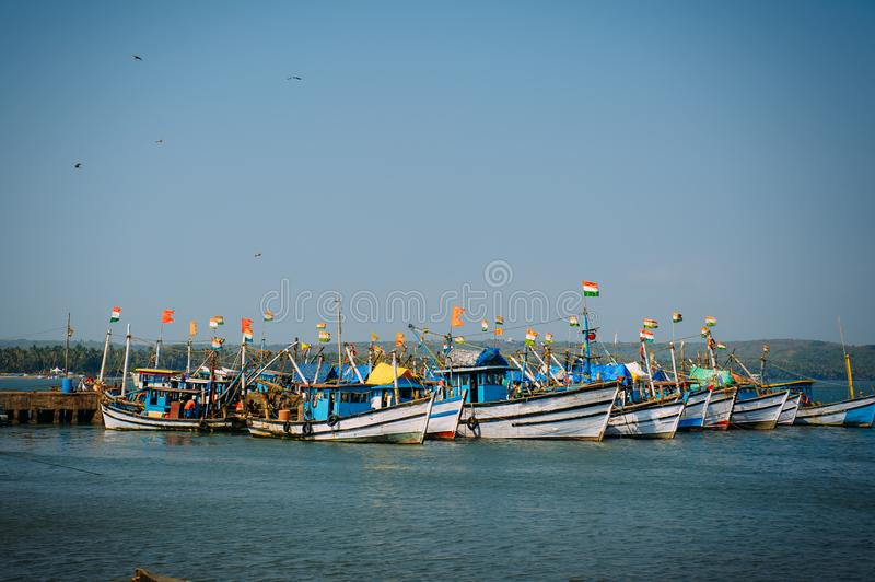 Colorful fishing boats with blue and white hulls and Indian flags on the masts, on the fishing pier in Goa. Wooden boats royalty free stock images