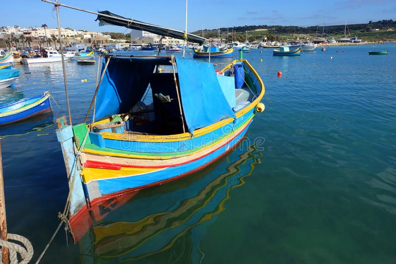 Colorful Fishing Boats Malta. Brightly painted traditional fishing boats, known as Iuzzu, anchored in the harbor of Marsaxlokk on the island of Malta royalty free stock images