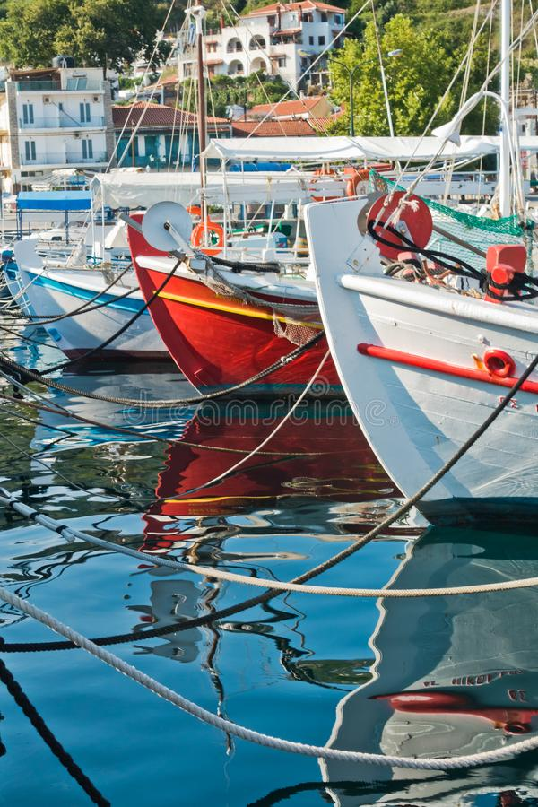 Colorful fishing boats and their reflections in a water of Skiathos harbor, island of Skiathos. Greece royalty free stock image