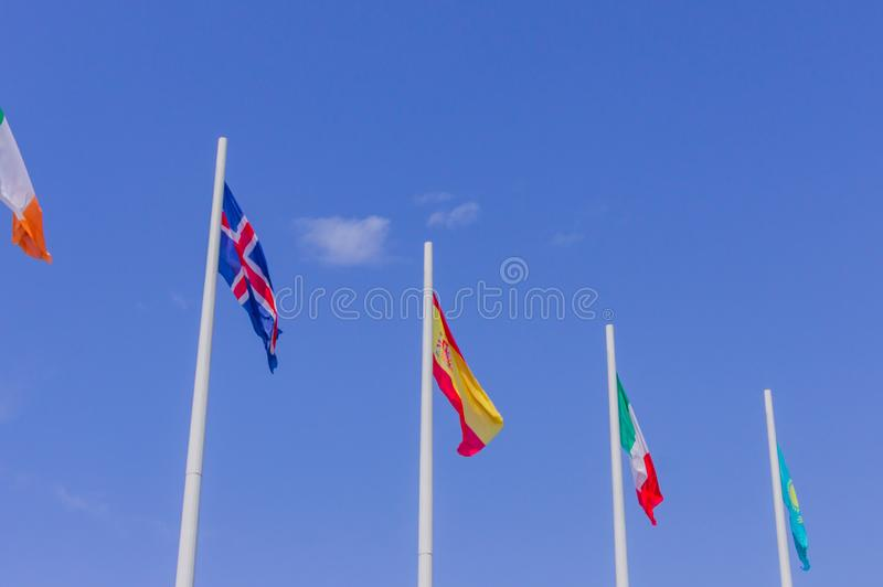 Colorful flags from different countries waving on blue sky background stock photo