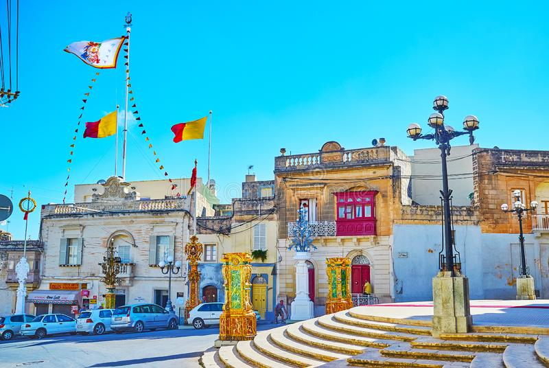 The colorful flags over the houses, Siggiewi, Malta. SIGGIEWI, MALTA - JUNE 16, 2018: The mansions in the central city street are decorated with colorful flags royalty free stock photos