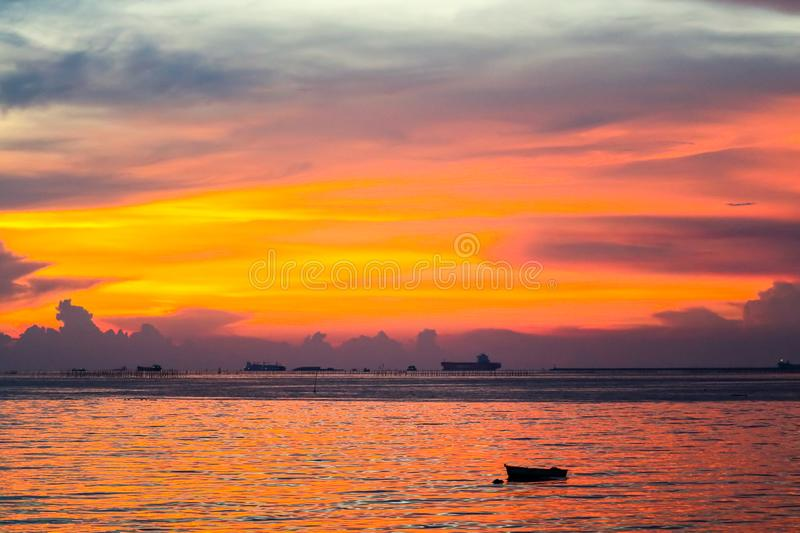 Colorful flame cloud sunset boat on sea and sky. Background, abstract, beauty, blue, bright, cloudscape, dark, dramatic, dusk, evening, fisherman, fishing, gold stock photo