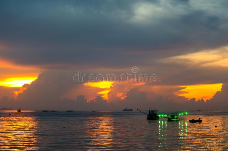 Colorful flame cloud sunset fisging boat on sea and sky. Background abstract beauty blue bright cloudscape dark dramatic dusk evening fisherman fishing gold royalty free stock photography
