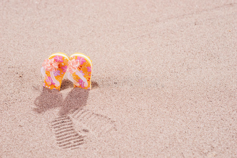 Colorful flip flops with flowers on the beach stock images