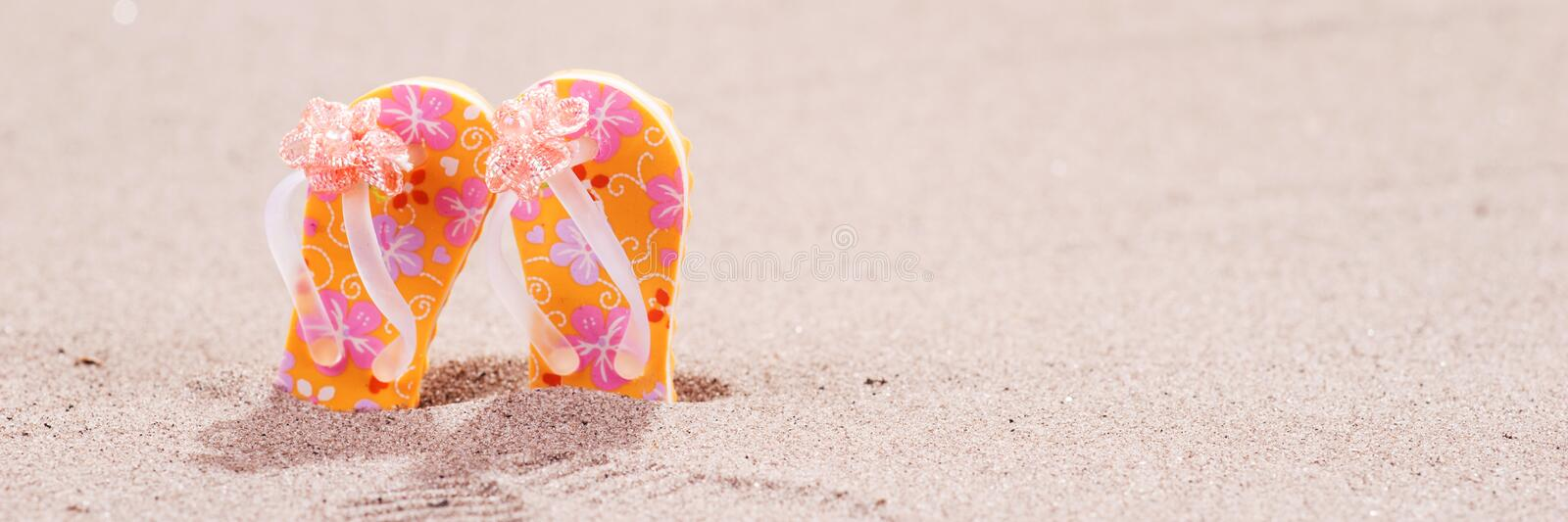 Colorful flip flops with flowers on the beach. Colorful flip flops with flowers on the sandy beach royalty free stock images
