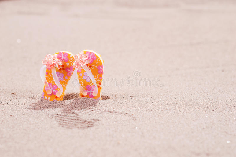 Colorful flip flops with flowers on the beach. Colorful flip flops with flowers on the sandy beach stock photography