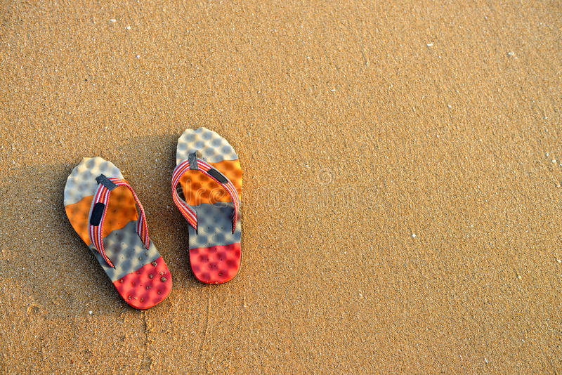 Colorful flip-flops on the sand. The shore of the Indian ocean royalty free stock photo