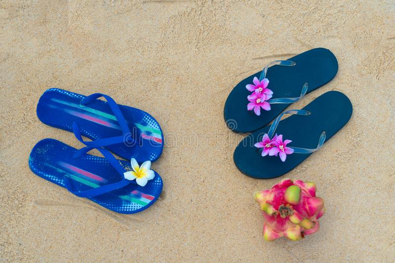 Colorful flip flops on the sandy beach. Male and female slippers stock photos