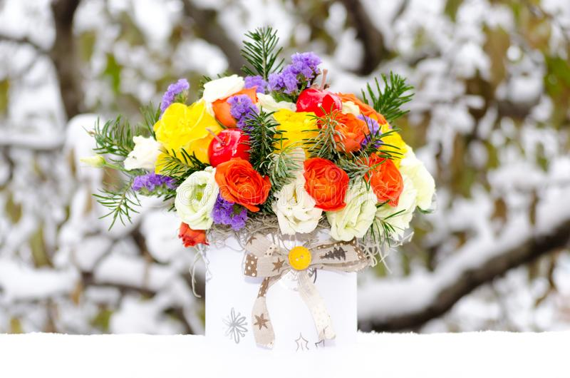 Colorful floral arrangement in the snow stock image